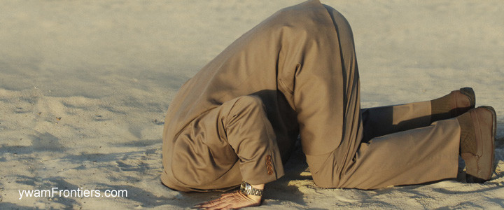 Photo of a man in a suit with his head buried in the sand