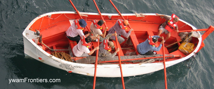 Photo of a group of people rowing a lifeboat